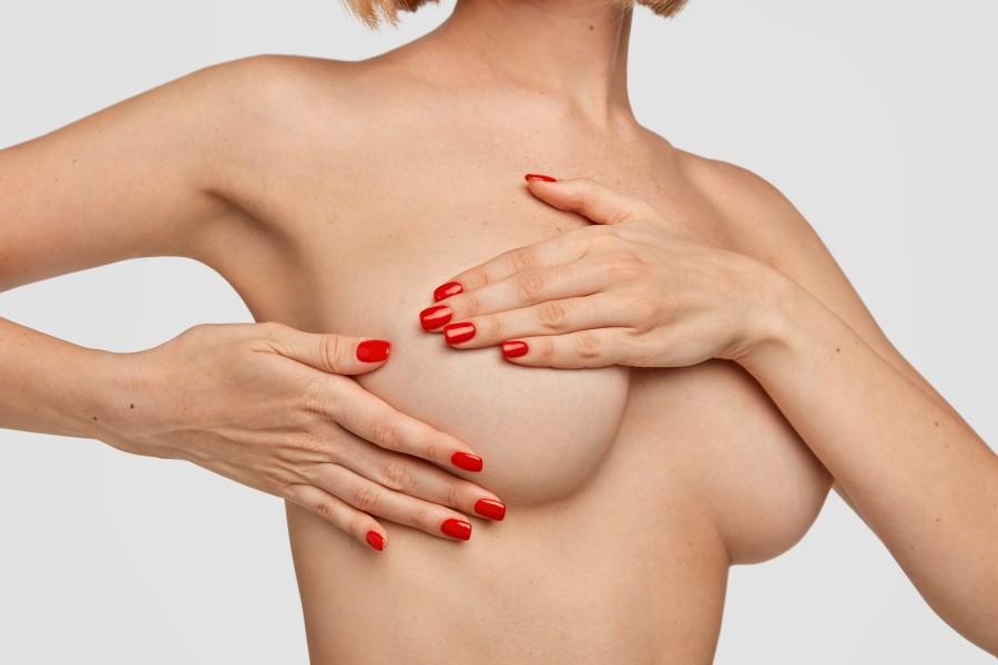 unrecognizable-woman-keeps-hands-on-bre